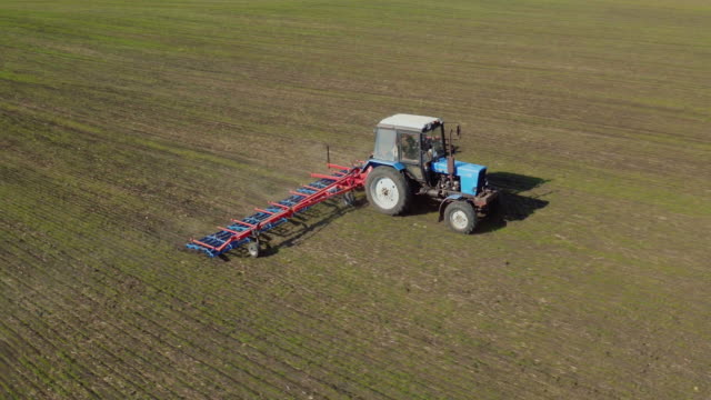 Field work in the spring. Tractor harrows the ground, side view, aerial survey video