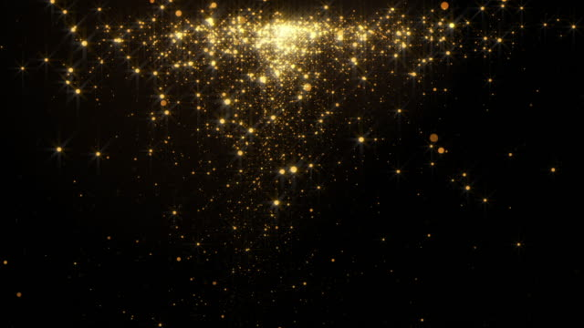 Fiery golden glowing star-like particles falling down over black background.