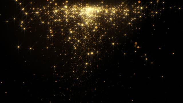 vídeos de stock e filmes b-roll de fiery golden glowing star-like particles falling down over black background. - glow