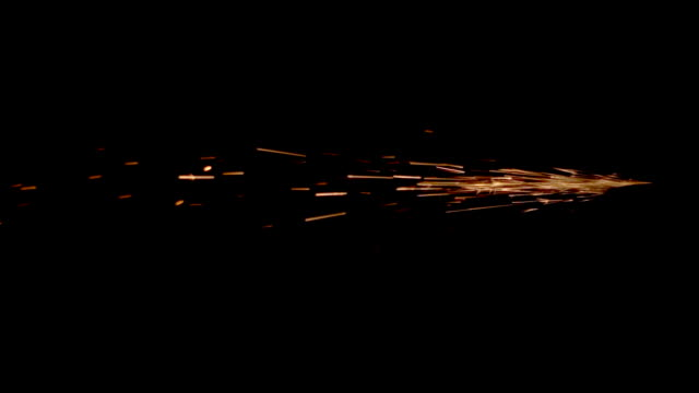 fiery sparks fly from one point on a black background - grindare video stock e b–roll