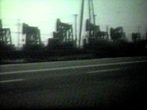 Fifties cars drive by oil wells-From 1950's film video