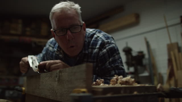 a fifty-something caucasian male woodworker in a plaid shirt uses a no.5 vintage hand plane along the edge of a red oak board creating wood shavings in a workshop - trociny wytworzony przedmiot filmów i materiałów b-roll