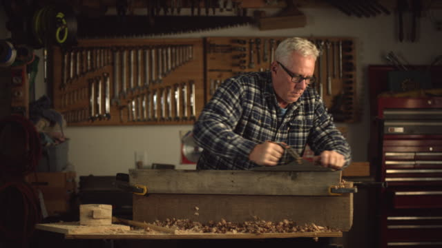 a fifty-something caucasian male woodworker in a plaid shirt uses a no.5 vintage hand plane along the edge of a red oak board creating wood shavings in a workshop - hobby filmów i materiałów b-roll