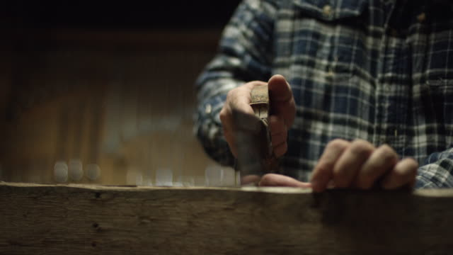 A Fifty-Something Male Woodworker in a Plaid Shirt Uses an Antique Hand Saw to Saw a Red Oak Board in a Workshop