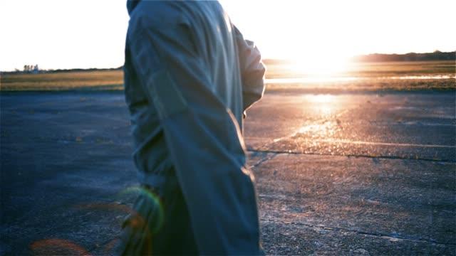 Fighter Pilot Walks Against Sunrise On The Airfield.