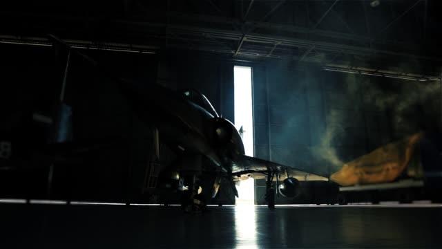 vídeos y material grabado en eventos de stock de avión de combate dentro de un hangar militar esperando el despliegue. - air force