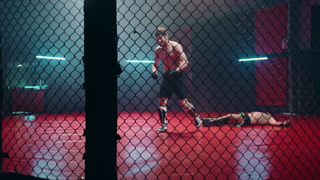 MMA fighters throwing punches in octagon. Knockout