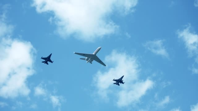 F16 fighting falcons flying with government airplane