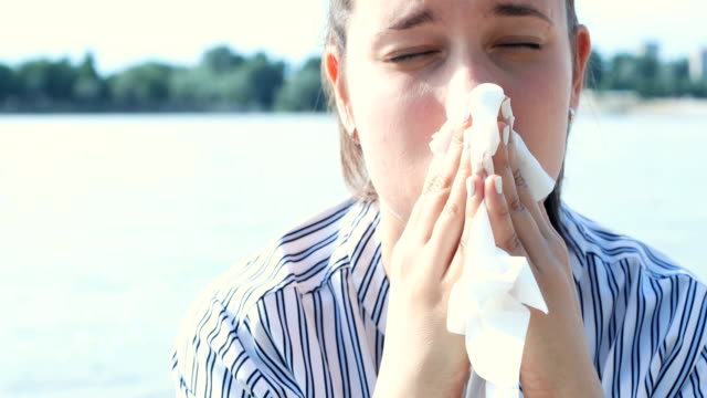 Fighting the flu Close-up shot of a woman applying napkin to her nose as she's fighting the flu. City scape across the river displayed in defocused background. season stock videos & royalty-free footage