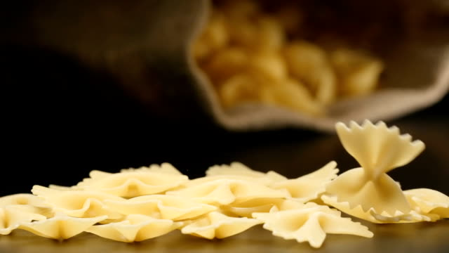 SLOW MOTION: Figural pasta (farfalle) fall near a lying cloth bag SLOW MOTION: Figural pasta (farfalle) fall near a lying cloth bag sac stock videos & royalty-free footage