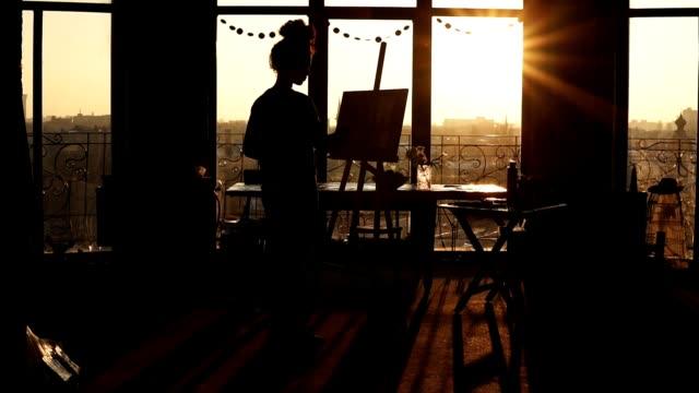 vídeos y material grabado en eventos de stock de una figura de artista femenina bajo la sombra de atardecer en el fondo basándose en caballete. video inspirador. - pintor artista