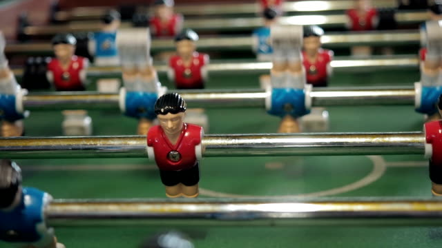figures of footballers move left and right people playing foosball. table soccer plaers. table football soccer game kicker close up