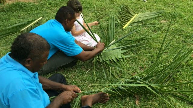 Fijian men teach young tourist girl how to create a basket from Coconut Palm video