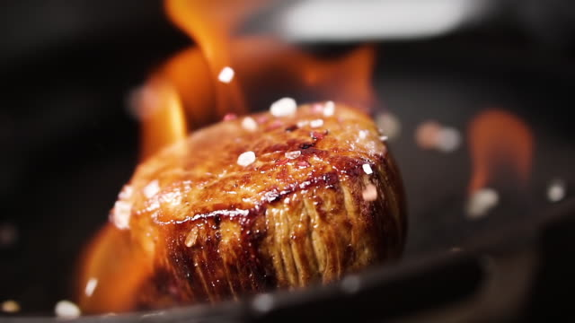 Filet mignon steak is fried in a pan with fire. Salt falls on a steak, slow motion.