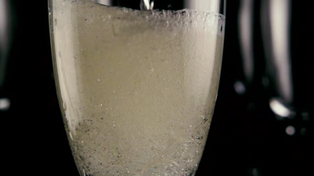 Fill a glass of champagne completely. Slow motion video