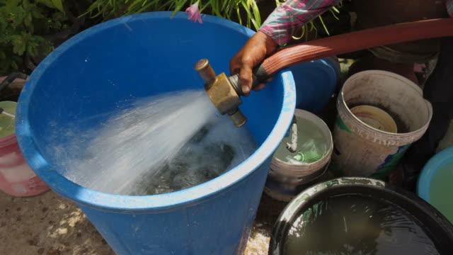 füllung wasser in ein blaues tank. - eimer stock-videos und b-roll-filmmaterial