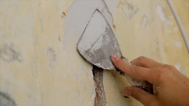 filling a hole in the wall with construction material,close up - muro video stock e b–roll