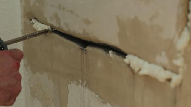 filling a wall crack with foam - poliuretano polimero video stock e b–roll
