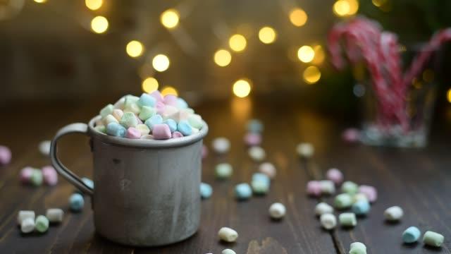 vídeos de stock, filmes e b-roll de caneca de alumínio de enchimento com marshmallow - chocolate quente