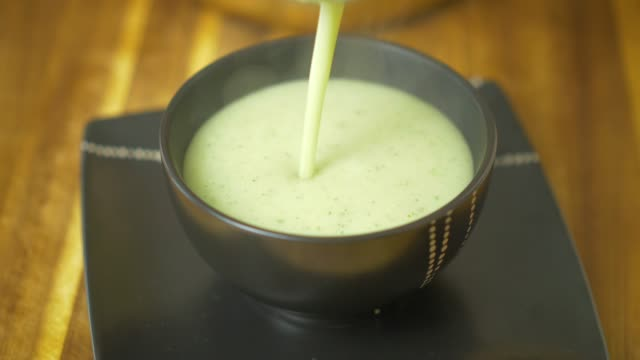 filling cauliflower soup into a black stoneware bowl