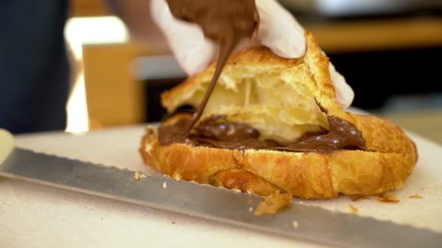 napełnianie rogalika kremem czekoladowym w lokalnej piekarni - francuska kuchnia filmów i materiałów b-roll