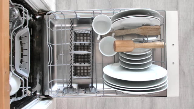 Filling dirty dishes in the dishwasher.Timelapse, FullHD A man puts dirty dishes in the dishwasher FullHD dishwasher stock videos & royalty-free footage