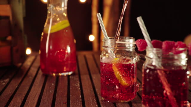 vídeos de stock e filmes b-roll de filling fresh homemade lemonade in a mason jar glass - limonada tradicional