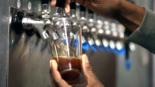 Filling glass with beer at micro brewery - video
