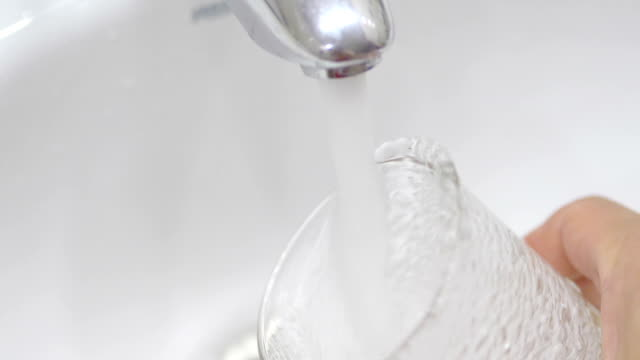 Filling glass with clean drinking water in slow motion 180fps High quality video of water filling glass with clean drinking water in slow motion 180fps faucet stock videos & royalty-free footage