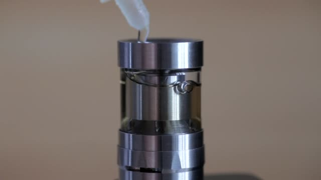 filling of vape tank or vaping atomizer with e-liquid, macro. juice for electronic cigarette - sok filmów i materiałów b-roll