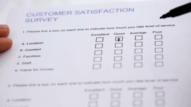 vídeos de stock, filmes e b-roll de preenchendo o formulário de pesquisa de satisfação do cliente - questionário