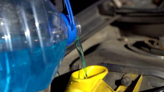 vídeos de stock e filmes b-roll de filling up a windshield washer tank of a car by antifreeze close up - cisterna água parada