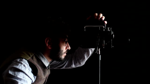 Film director in old fashioned clothes holding camera and megaphone video