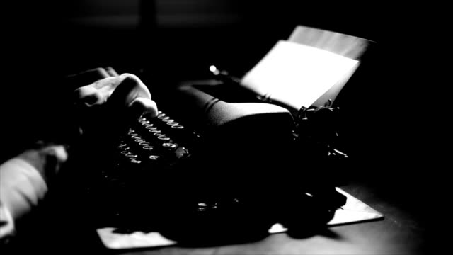 Film Noir Typing Light focuses on the hands of a man typing on a vintage 40's style manual typewriter. Film Noir Lighting and affect. typewriter stock videos & royalty-free footage