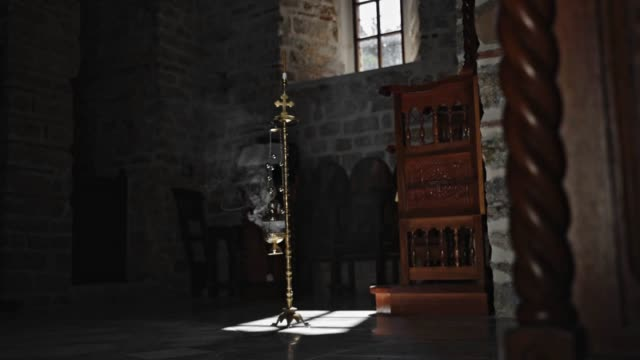 a film shot of an orthodox church burning candle - candeliere video stock e b–roll