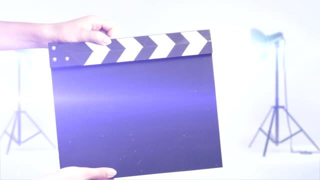 vidéos et rushes de film ardoise dans un studio photo arrière-plan - ardoise