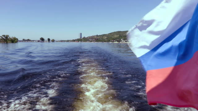 Filming from the stern of the ship. Summer river landscape. The Volga river in Saratov, Russia. Russian flag, the tricolor. Road bridge between the cities of Saratov and Engels video