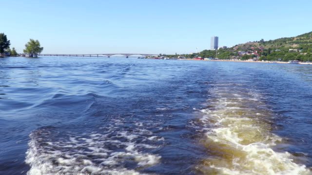 Filming from the stern of the ship. Summer river landscape. The Volga river in Saratov, Russia.  Road bridge between the cities of Saratov and Engels. The sound of the boat motor. Footage clip 4K video
