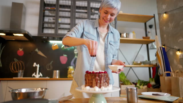 Final touch for a perfect cake Young woman making a cake at her kitchen. blue hair stock videos & royalty-free footage