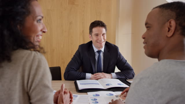 Financial advisor consulting a couple in his office video
