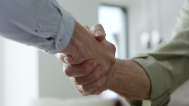Financial advisor shaking hands with older couple Financial advisor shaking hands with couple in livingroom guidance stock videos & royalty-free footage