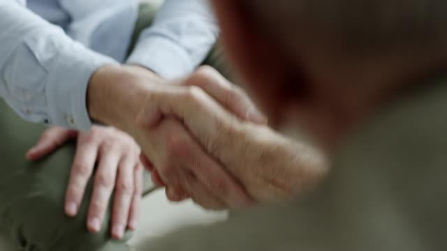 Conseiller financier, serrant la main de vieux couple - Vidéo