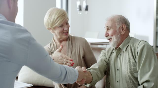 vidéos et rushes de conseiller financier, serrant la main de vieux couple - conseiller financier