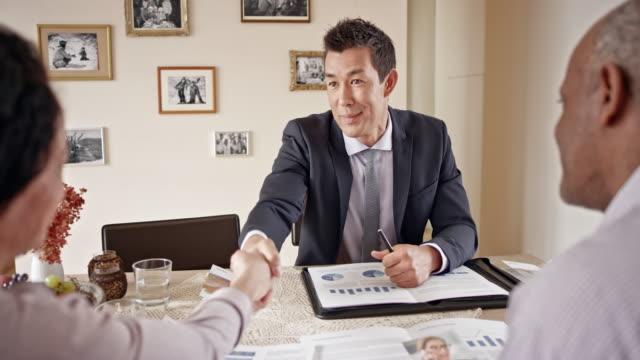 自宅で年配のカップルと握手金融アドバイザー - ファイナンシャルアドバイザー点の映像素材/bロール