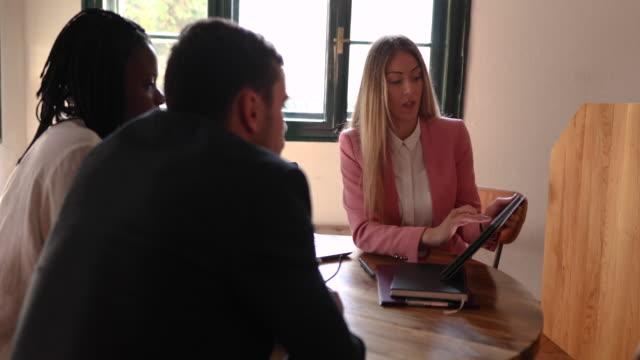 vídeos y material grabado en eventos de stock de asesor financiero que muestra a la pareja preocupada diferentes esquemas de inversión disponibles para ellos - planificación financiera