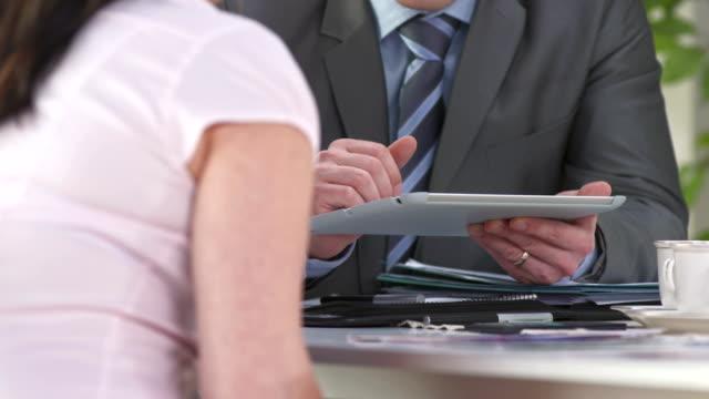 hd: financial advisor using tablet computer - insurance bildbanksvideor och videomaterial från bakom kulisserna