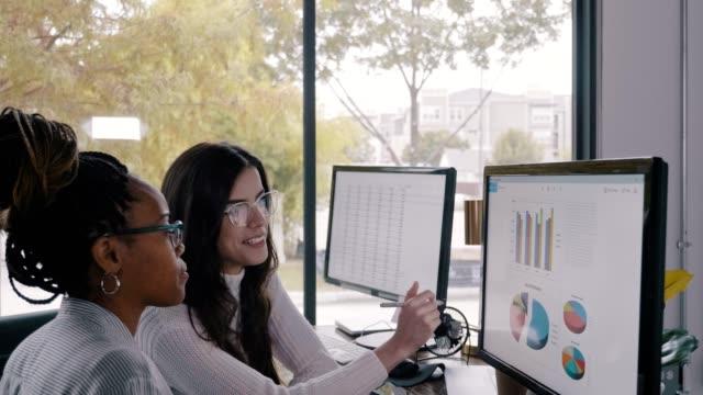 vídeos y material grabado en eventos de stock de analistas financieros examinan gráficos y gráficos financieros juntos - mirar