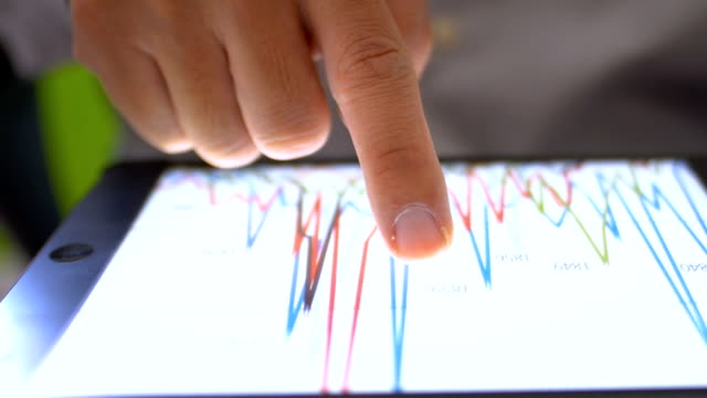 vídeos de stock e filmes b-roll de financial analysts see charts and graphs on digital tablet - examinar