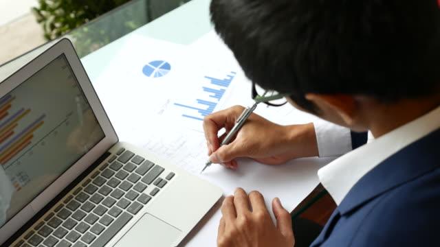 vídeos de stock, filmes e b-roll de os analistas financeiros ver tabelas e gráficos na tela do laptop - estratégia