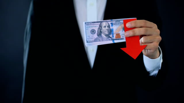 Financial consultant holding dollar banknotes showing thumbs down, falling